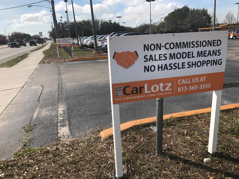 Site signs for CarLotz along busy roadway