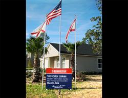 Custom Site Sign with Flags for a National Home Builder Installed by FASTSIGNS Baymeadows.