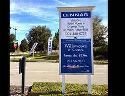 Custom Site Sign with Flags or a Home Builder Produced and Installed by FASTSIGNS Baymeadows.