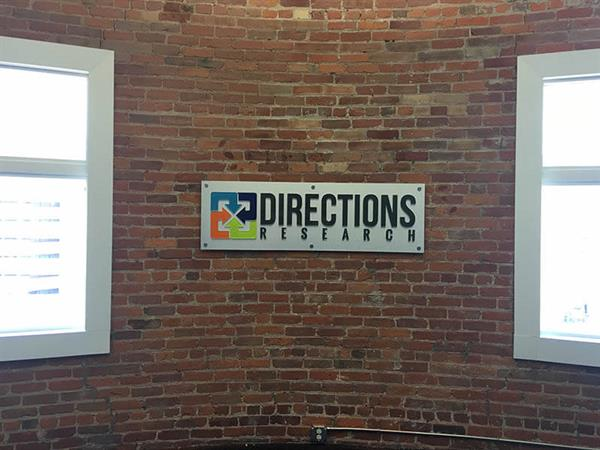 Directions Research Lobby Logo Sign on Brick